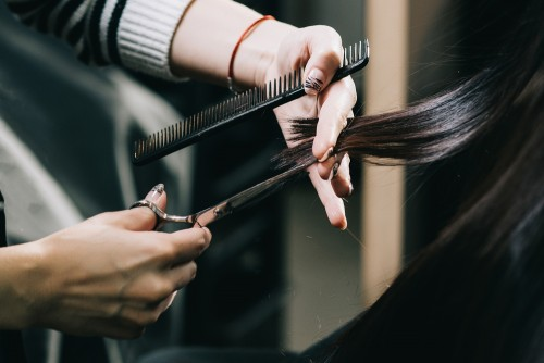 cosmetologist cutting hair