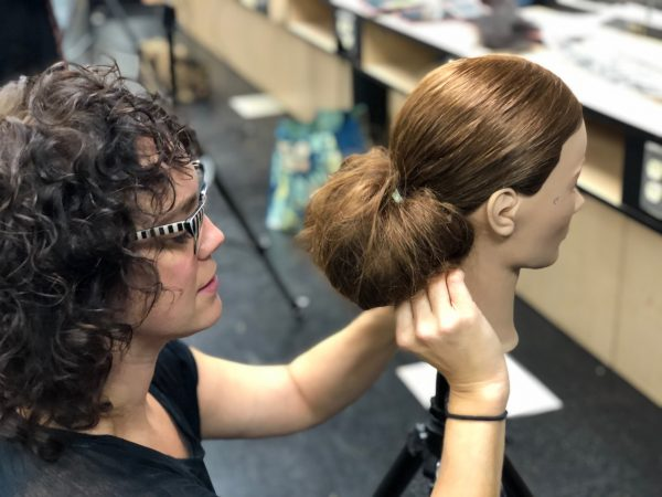 Female student styling mannequin hair