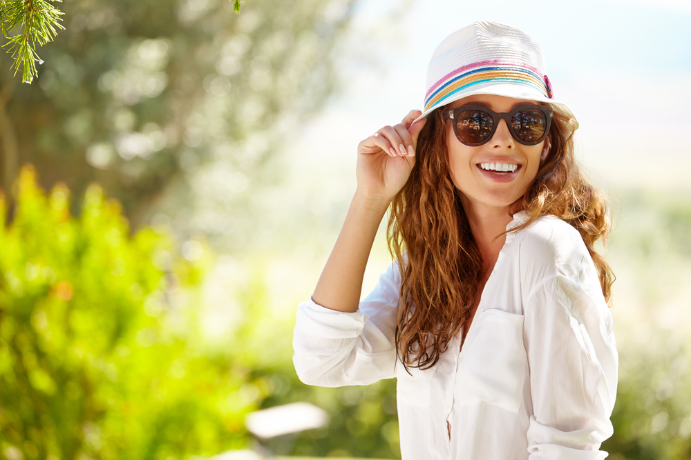 woman smiling with a summer hat